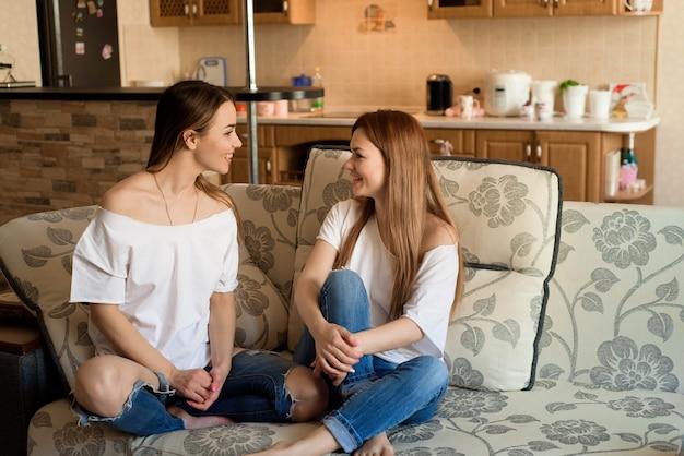 Duas amigas alegres bonitas novas na calças de ganga que senta-se no sofá em casa que ri.