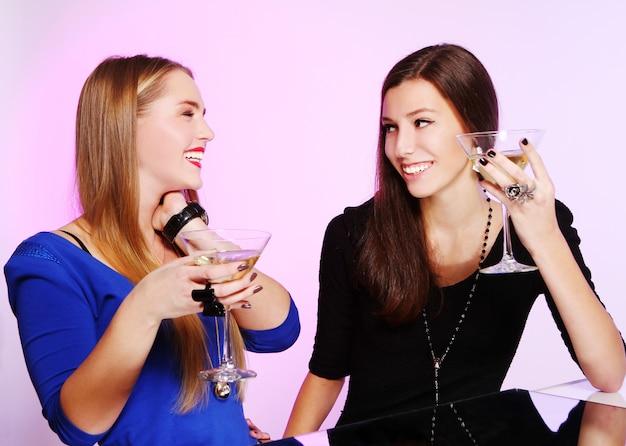 Duas amigas alegres com cocktails coloridos