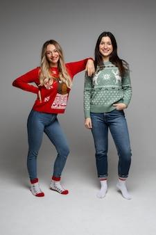 Duas amigas alegres de cabelos compridos, loira e morena, vestindo suéteres quentes de inverno, posando no estúdio cinza