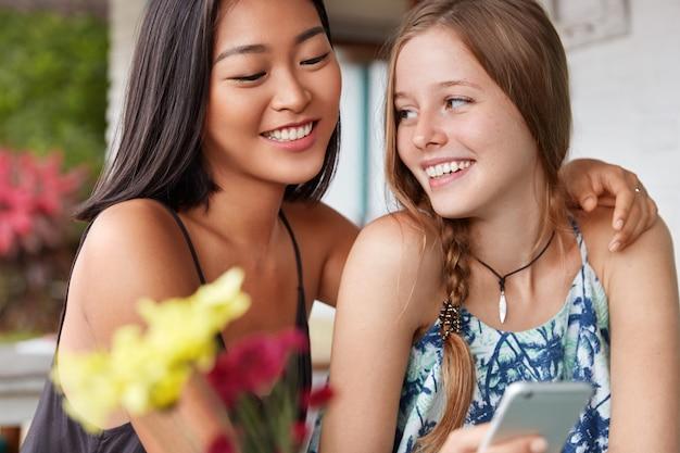 Duas amigas alegres de diferentes nacionalidades se abraçam, se divertem juntas, descansam em um café, seguram um smartphone moderno