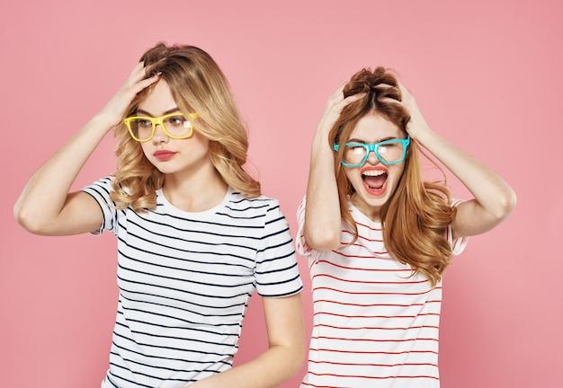 Duas amigas alegres em camisetas listradas estão lado a lado em um fundo rosa