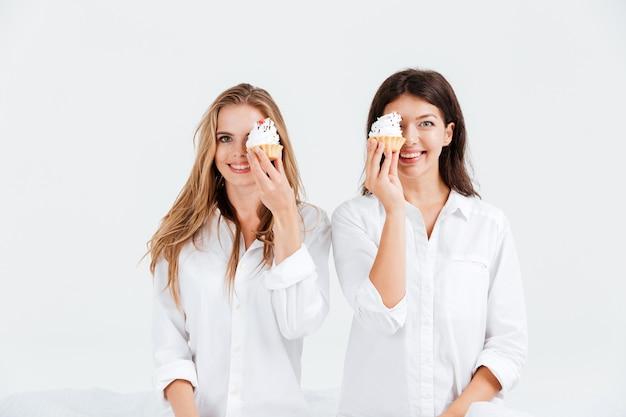 Duas amigas alegres segurando bolinhos doces enquanto estão sentadas na cama
