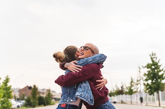 Duas amigas amigas dando um abraço uma à outra.
