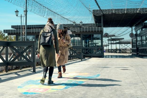 Duas amigas andando em um parque e brincando de amarelinha na calçada, adolescência, infância