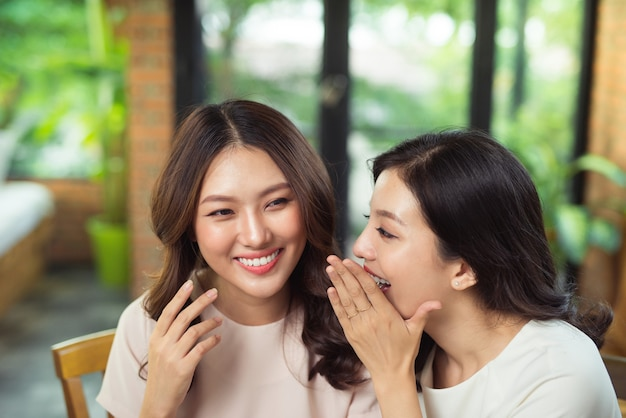 Duas amigas asiáticas conversando e fofocando