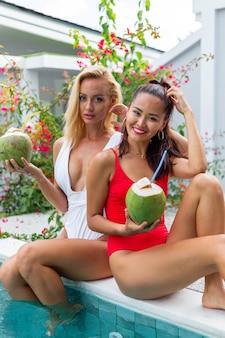 Duas amigas asiáticas e caucasianas com maquiagem à beira da piscina em uma villa amigas com cocos nas férias perto da piscina azul e árvore de flores