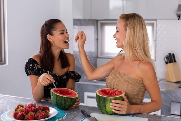 Duas amigas asiáticas e caucasianas, comendo melancia e frutas tropicais de rambutan na cozinha. fêmea sair juntos em casa, conversar e sorrir. conceito amizade estilo de vida saudável