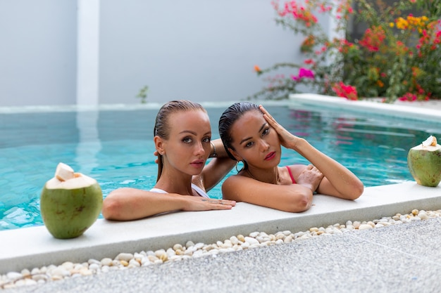 Duas amigas asiáticas e caucasianas maquiadas na piscina da villa