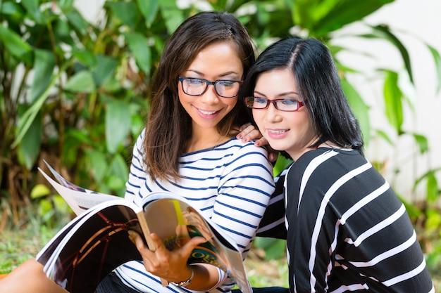 Duas amigas asiáticas lendo revista
