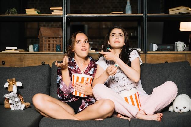 Duas amigas assistindo televisão encolhendo os ombros