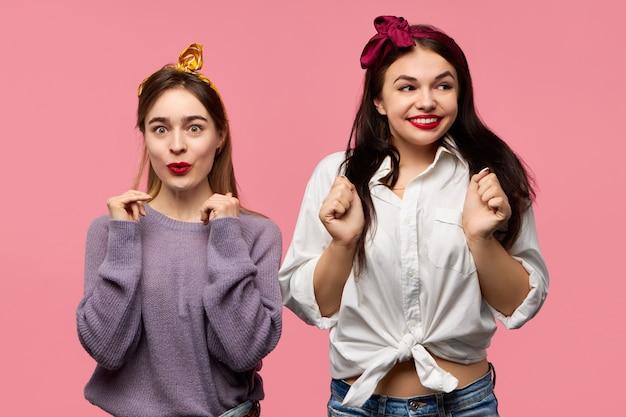 Duas amigas bonitas e elegantes, vestidas com estilo, estando de bom humor, sorrindo e rindo, animadas com notícias incríveis