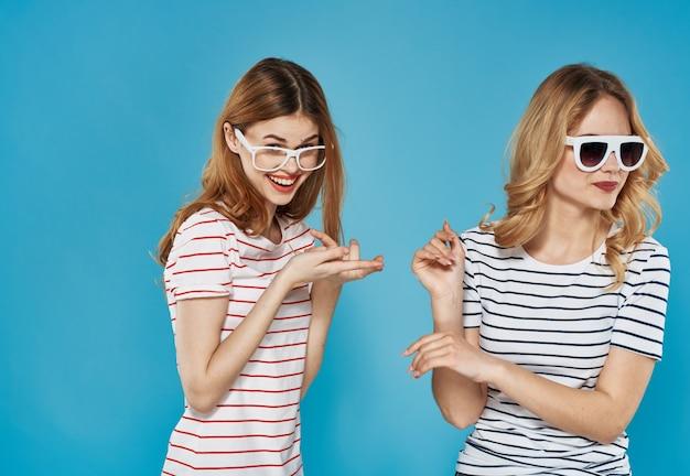 Duas amigas bonitas gesticulam com as mãos divertidas, amizade, alegria, estilo de vida