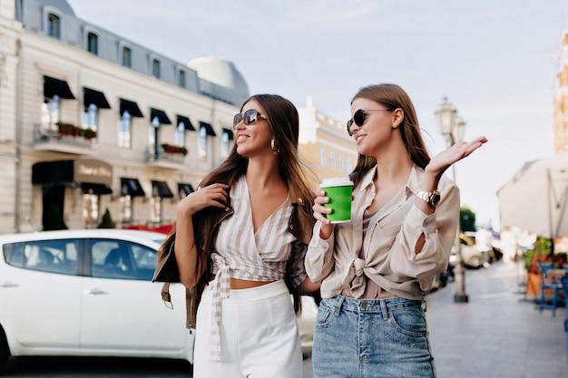Duas amigas brancas caminhando juntos na cidade enquanto bebem café e conversam.