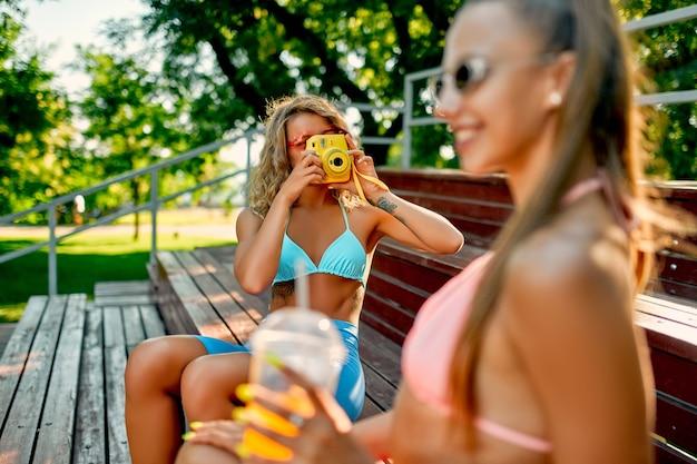 Duas amigas brancas em trajes de banho bebem suco ou limonada no estádio