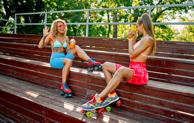 Duas amigas brancas em trajes de banho bebem suco ou limonada no parque