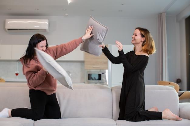 Duas amigas brigam alegremente com almofadas no sofá em casa. o conceito de felicidade e juventude. foto de alta qualidade