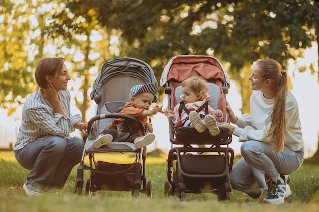 Duas amigas caminhando com carrinhos de bebê e seus filhos no parque