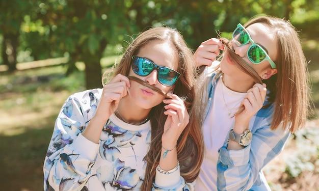 Duas amigas com óculos de sol se divertindo fazendo bigodes com seus longos cabelos. conceito de relaxamento e lazer.