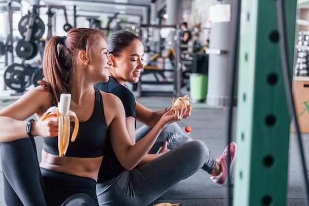 Duas amigas com roupas esportivas estão na academia, arrancando frutas e fazendo uma pausa.