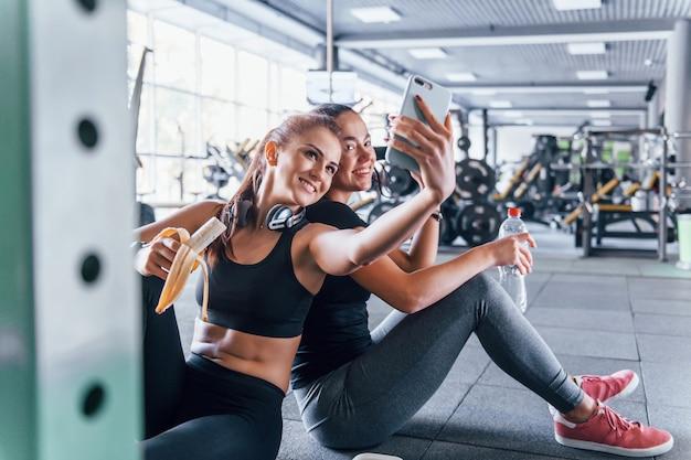 Duas amigas com roupas esportivas estão na academia, arrancando frutas e tirando uma selfie.