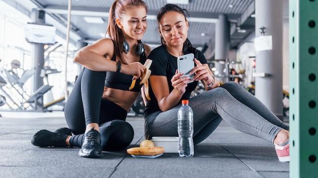 Duas amigas com roupas esportivas estão no ginásio, arrancando frutas e usando o telefone.