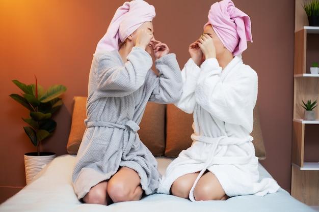 Duas amigas com toalhas na cabeça, fazendo tratamentos de spa em casa na cama