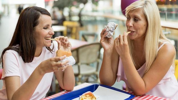 Duas amigas comendo hambúrgueres com batatas fritas em restaurante