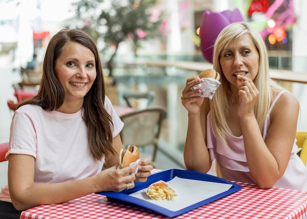 Duas amigas comendo hambúrgueres em restaurante