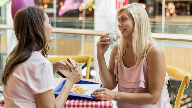 Duas amigas comendo hambúrgueres juntas em restaurante