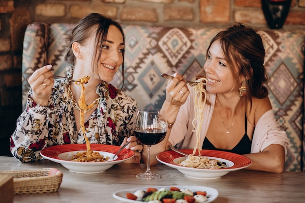 Duas amigas comendo macarrão em um restaurante italiano
