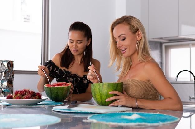 Duas amigas comendo melancia e frutas tropicais de rambutan na cozinha