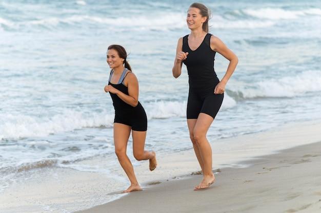 Duas amigas correndo juntas na praia