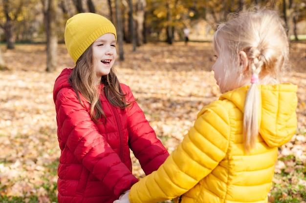 Duas amigas de mãos dadas em um dia ensolarado de outono.