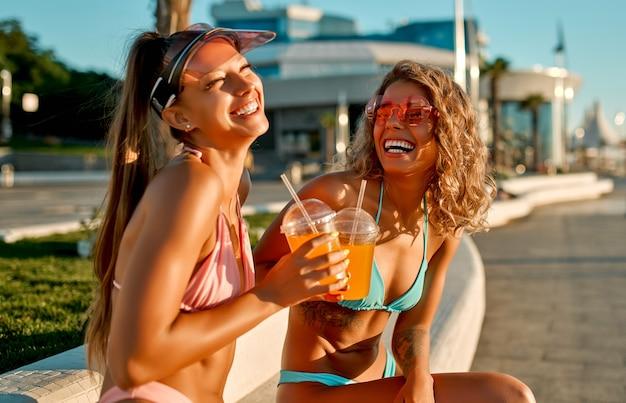 Duas amigas de mulheres brancas em trajes de banho bebem suco ou limonada e patins perto da praia.