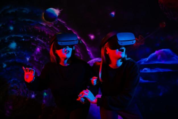 Duas amigas de óculos virtuais estão de mãos dadas na sala de jogos sob luz de néon