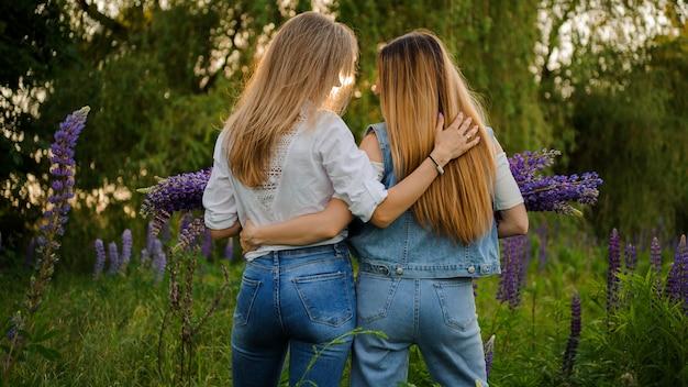 Duas amigas de pé no campo com buquês de flores roxas