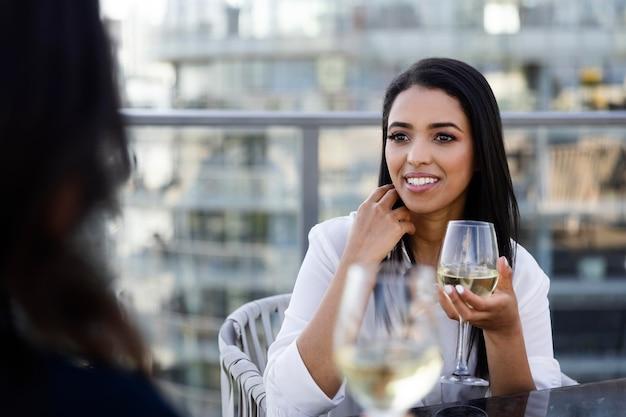 Duas amigas degustando vinho em um terraço na cobertura