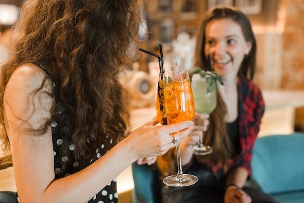 Duas amigas desfrutando de coquetel no bar