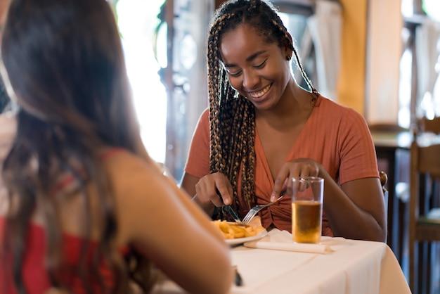 Duas amigas desfrutando de uma refeição juntas em um restaurante.