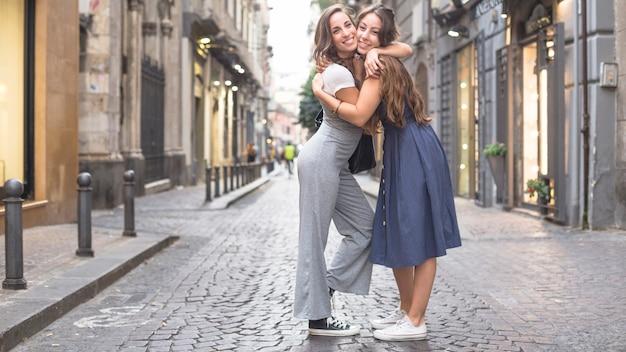 Duas amigas elegantes em pé na rua, abraçando uns aos outros