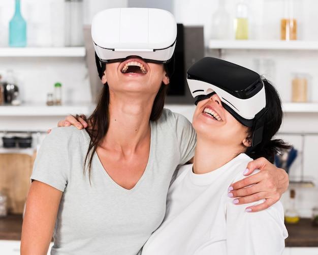 Duas amigas em casa se divertindo com um fone de ouvido de realidade virtual