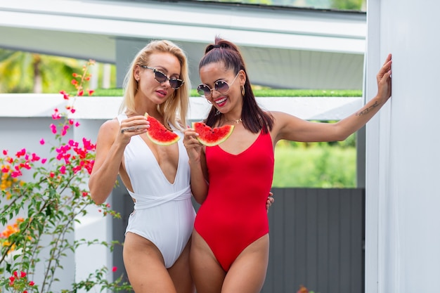 Duas amigas em maiô asiáticas e caucasianas em uma vila com melancia. férias em países tropicais. frutas frescas