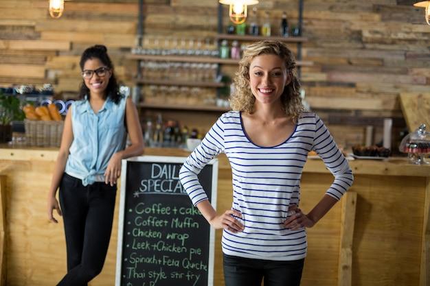 Duas amigas em pé com placa de menu perto de balcão