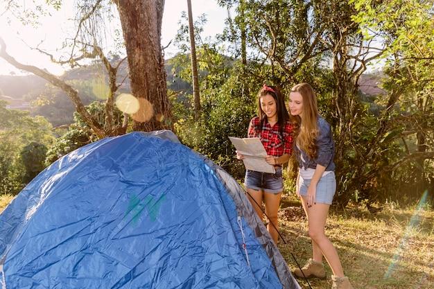 Duas amigas em pé perto da tenda, olhando para o mapa