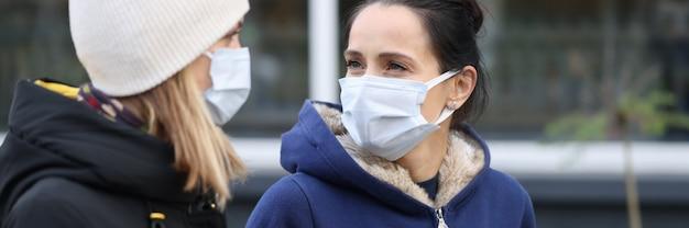 Duas amigas em roupas quentes e chapéu caminham ao longo da rua usando retrato de máscaras protetoras.