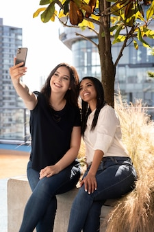 Duas amigas em um terraço tirando uma selfie