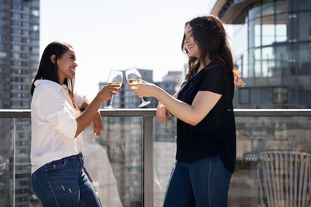 Duas amigas em um terraço tomando vinho e conversando