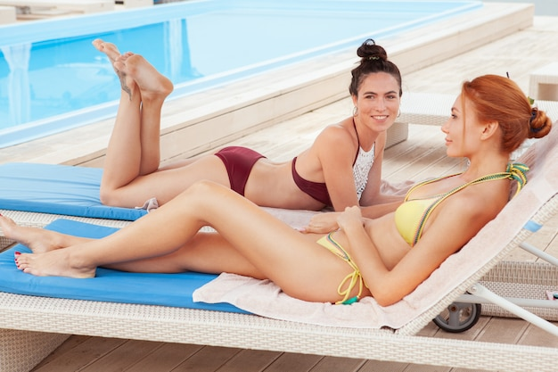 Duas amigas encantadoras relaxantes na piscina