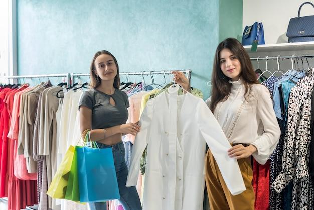 Duas amigas escolhendo uma roupa nova em uma butique de roupas. compra e venda