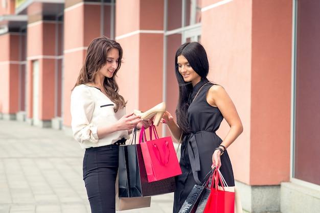 Duas amigas estão se mostrando nova compra no shopping.